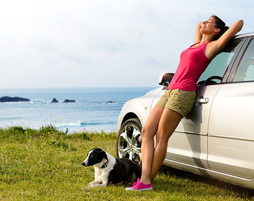 Dog lies next to a woman leaning on a car.